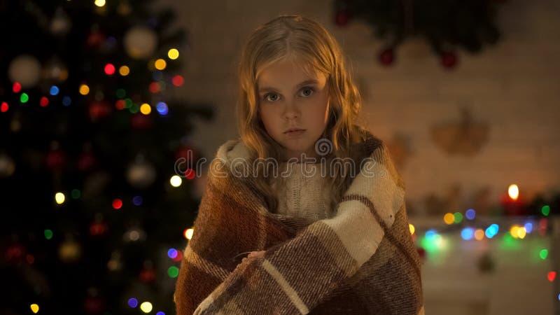 Verlaten kind die met plaid aan camera kijken die nieuwe familie, Kerstmistijd wachten royalty-vrije stock afbeelding