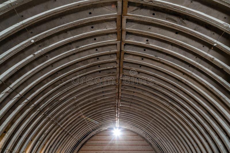 Verlaten leeg pakhuis, oude rustieke metaalstructuur met metaaldakwerk, binnenlands van de oude commerciële fabrieksbouw stock foto's