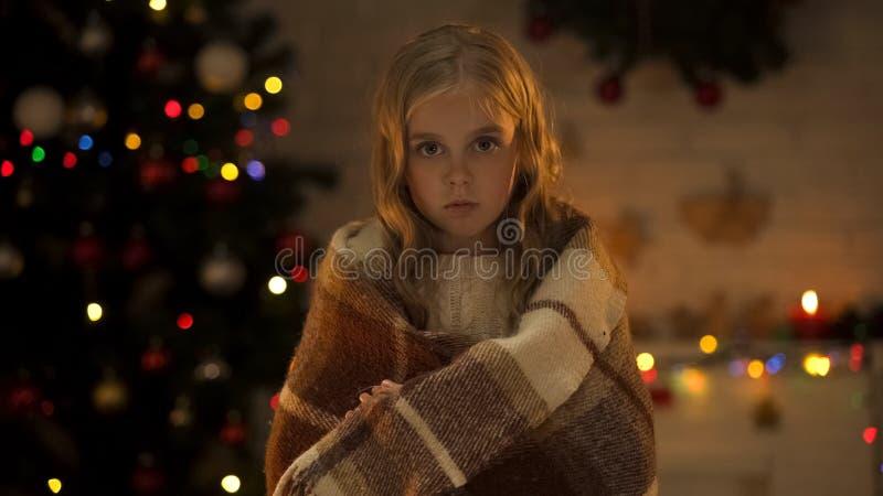 Verlaten meisje die met plaid aan camera kijken die nieuwe familie, Kerstmistijd wachten stock fotografie