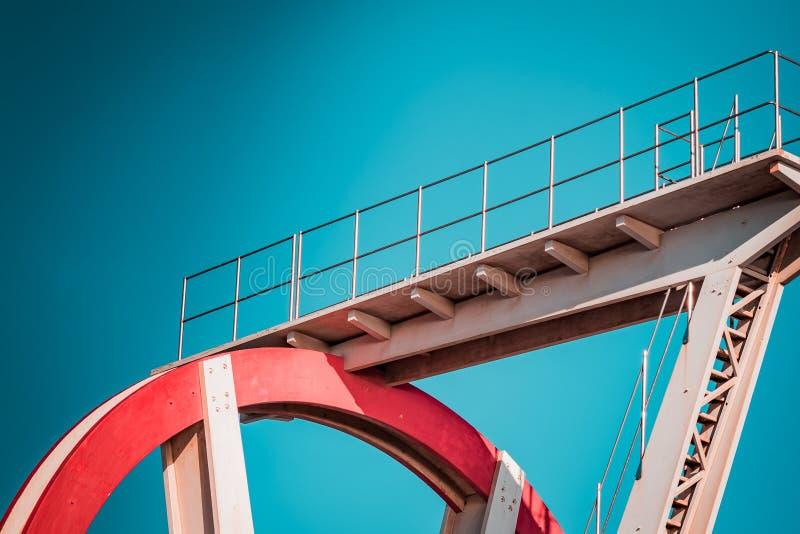 Verlaten metaal het duiken structuur Iconische industriële en sportenarchitectuur, witte en rode staalelementen op een diepe blau stock afbeeldingen