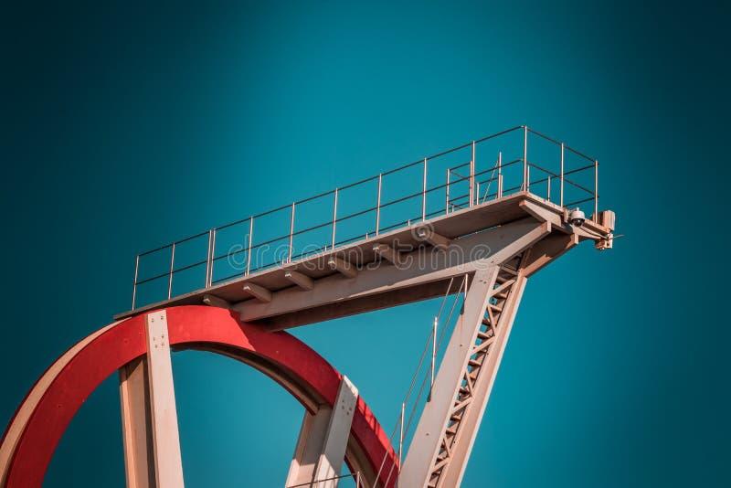 Verlaten metaal het duiken structuur Iconische industriële en sportenarchitectuur, witte en rode staalelementen op een diepe blau royalty-vrije stock fotografie