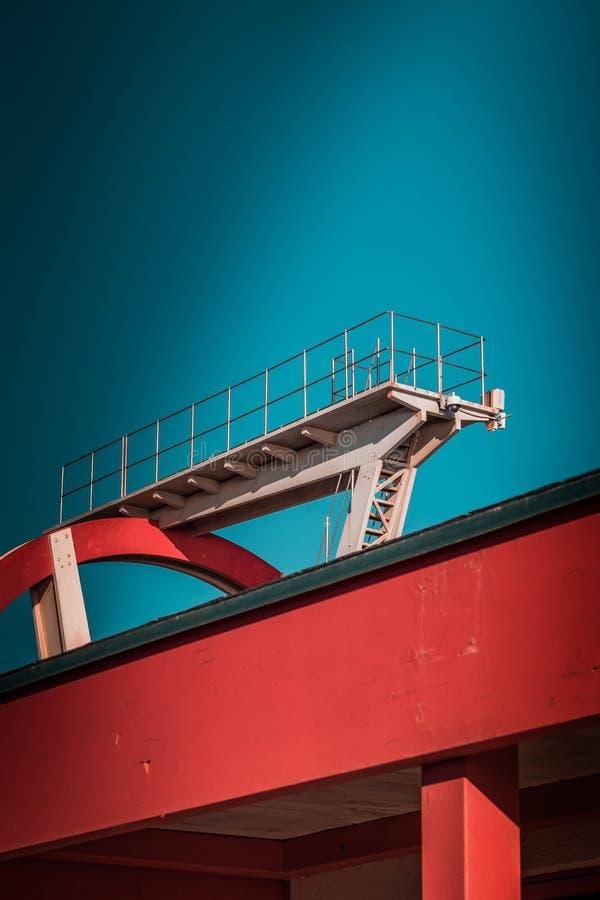 Verlaten metaal het duiken structuur Iconische industriële en sportenarchitectuur, witte en rode staalelementen op een diepe blau stock foto