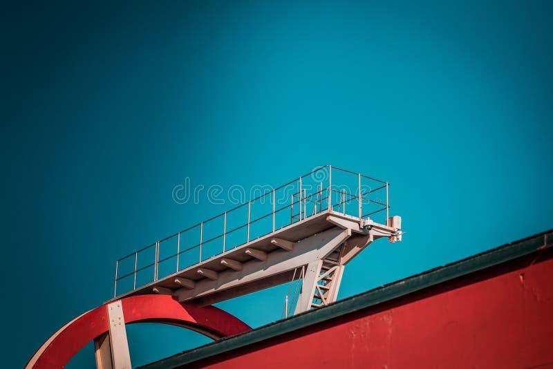 Verlaten metaal het duiken structuur Iconische industriële en sportenarchitectuur, witte en rode staalelementen op een diepe blau royalty-vrije stock afbeelding