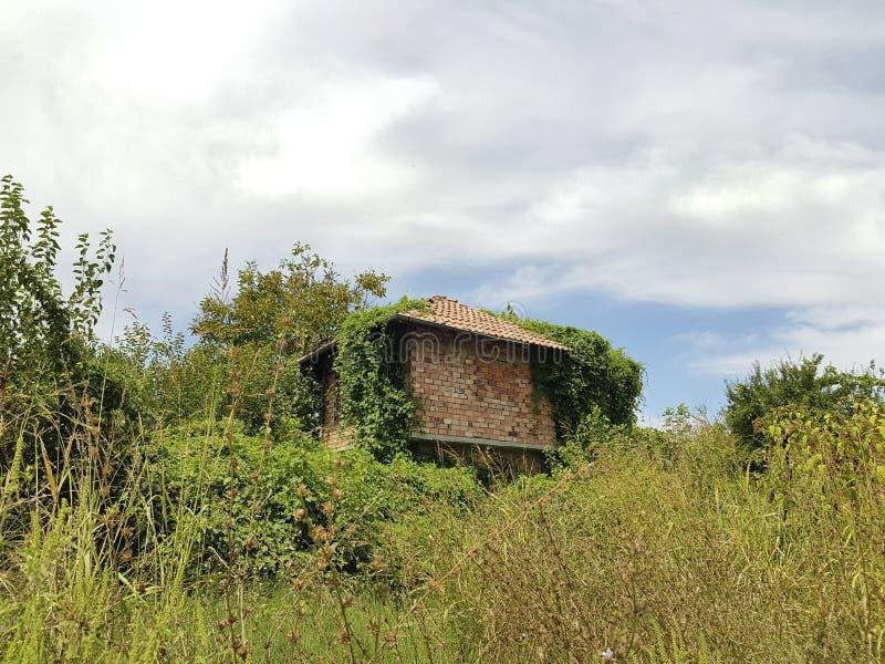 Verlaten onvolledig huis tussen bomen en gras en hemel royalty-vrije stock fotografie