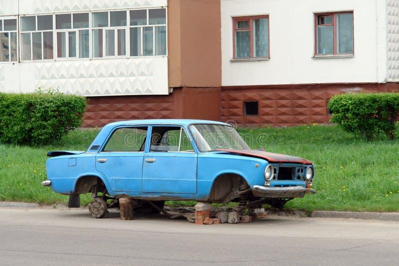 Verlaten oude blauwe gedemonteerde auto op straat dichtbij huis Oude auto met verwijderde wielen, vandalisme - Beeld royalty-vrije stock foto's