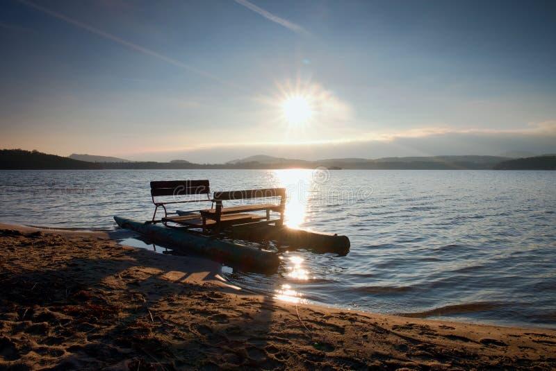 Verlaten oude roestige die pedaalboot op zand van strand wordt geplakt Golvende waterspiegel, eiland op horizon De herfst zonnig  stock foto's