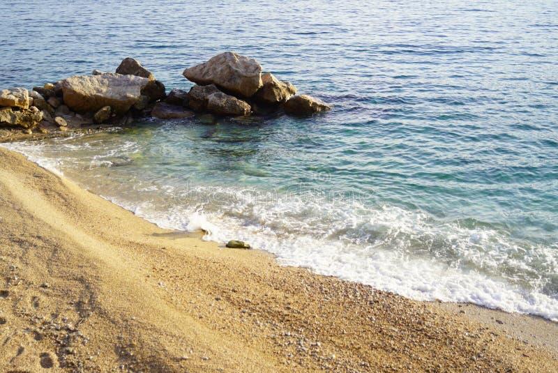 Verlaten overzees die strand, met kleine gele kiezelstenen wordt behandeld stock afbeelding