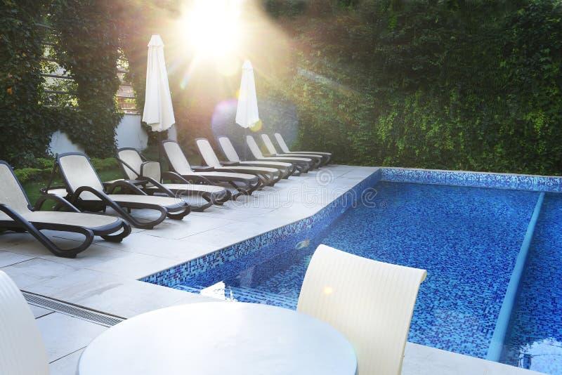 Verlaten pool en zonlanterfanters door de pool in de zachte stralen van de ochtendzon Plaats van rust en ontspanning, royalty-vrije stock afbeelding