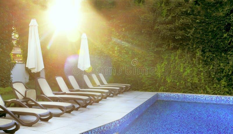 Verlaten pool en zonlanterfanters door de pool in de zachte stralen van de ochtendzon Plaats van rust en ontspanning, de zomerste royalty-vrije stock afbeeldingen