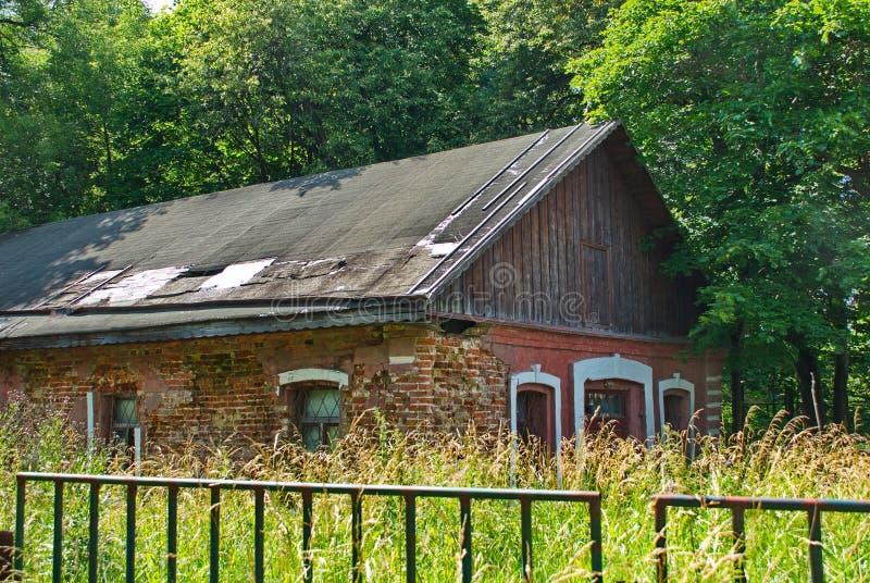 Verlaten rood die baksteenhuis door bomen en gras wordt omringd stock afbeeldingen