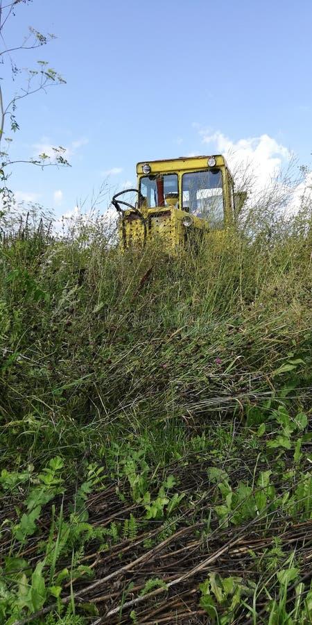 Verlaten tractor op een overwoekerd gebied stock fotografie