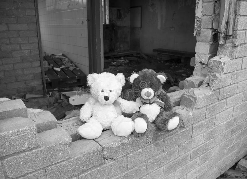 Verlaten Verlaten de Bouwmuur van Teddy Bears Sitting On Smashed in Zwart & Wit stock fotografie