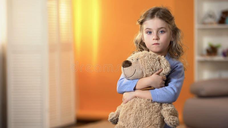 Verlaten verstoord krullend meisje favoriete teddybeer houden die voelend droevig in weeshuis royalty-vrije stock foto