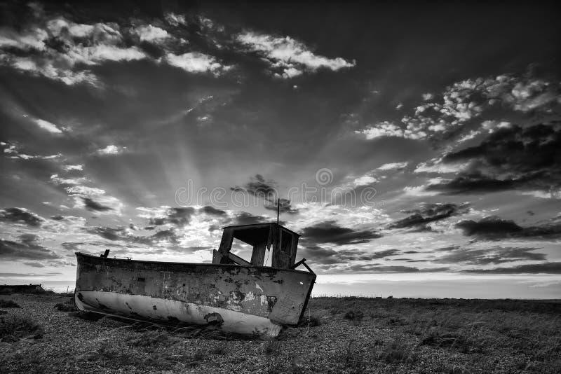 Verlaten vissersboot op strand zwart-wit landschap bij zon stock afbeeldingen