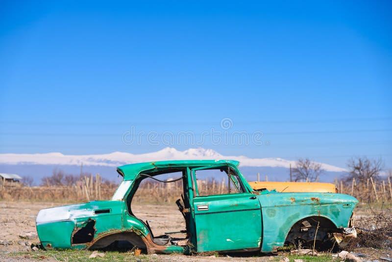 Verlaten wrak van een oude groene Sovjet Russische auto in het midden van droge landbouwgrond in Zuidelijk Armenië royalty-vrije stock afbeelding