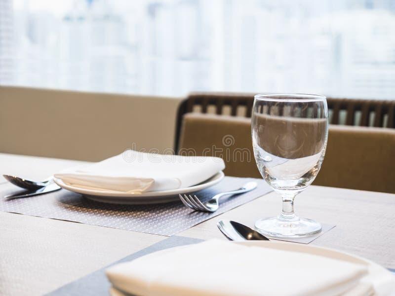 Verlegen Sie Abendessensatz mit Plattenserviette und Glas Restauranthintergrund stockbilder