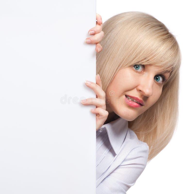 Verlegene junge Frau, die weißes leeres Papier anhält lizenzfreie stockbilder