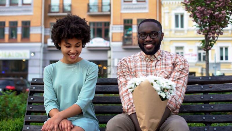 Verlegene Paare, die auf Bank mit Blumen, erstes Datum, Neigungsgefühle sitzen stockbilder