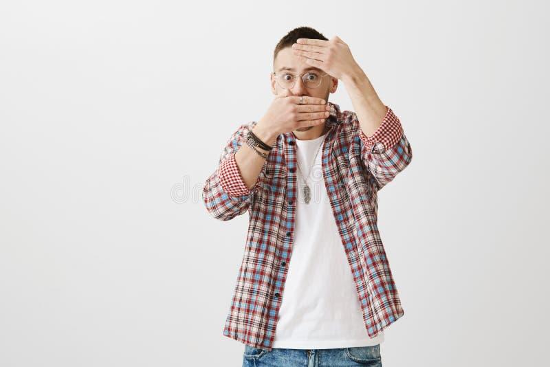 Verlegener junger Kerl in den Gläsern, die Gesicht mit Palmen bedecken und durch sie spähen, Schrecken ausdrücken und ungeschickt lizenzfreies stockfoto