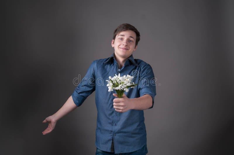 Verlegener junger Mann im blauen Hemdholdingblumenstrauß mit den Schneeglöckchen, Kamera und das Lächeln betrachtend lizenzfreies stockbild