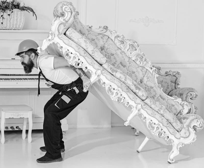 Verlegungskonzept Kurier liefert Möbel im Falle sich bewegen heraus, Verlegung Lader bewegt Sofa, Couch Mann mit Bart stockfotografie