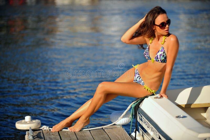 Verleidelijk model die modieuze swimwear en zonnebril dragen en op de rand van motorboot stellen stock fotografie