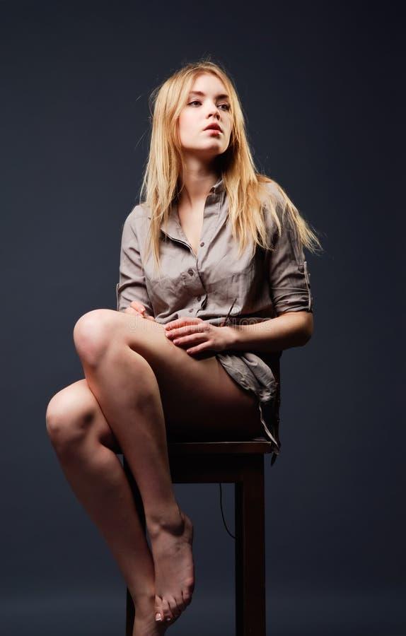 Verleidelijk portret van jonge vrouwenzitting op stoel stock afbeelding