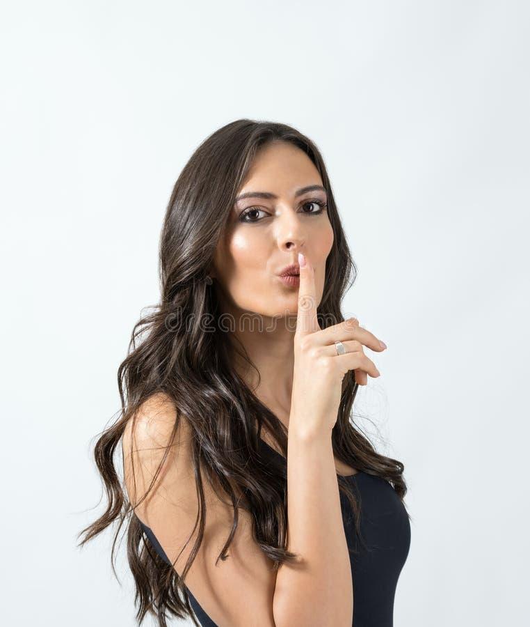 Verleidelijke aantrekkelijke gelooide schoonheidsvrouw met vinger over haar gebaar van de mondstilte stock foto's