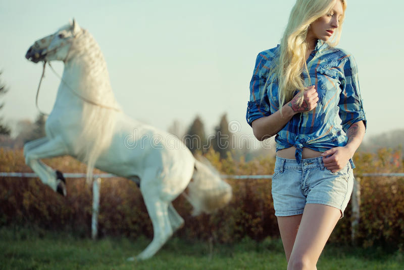 Verleidelijke blondeschoonheid met majestueus paard royalty-vrije stock foto's