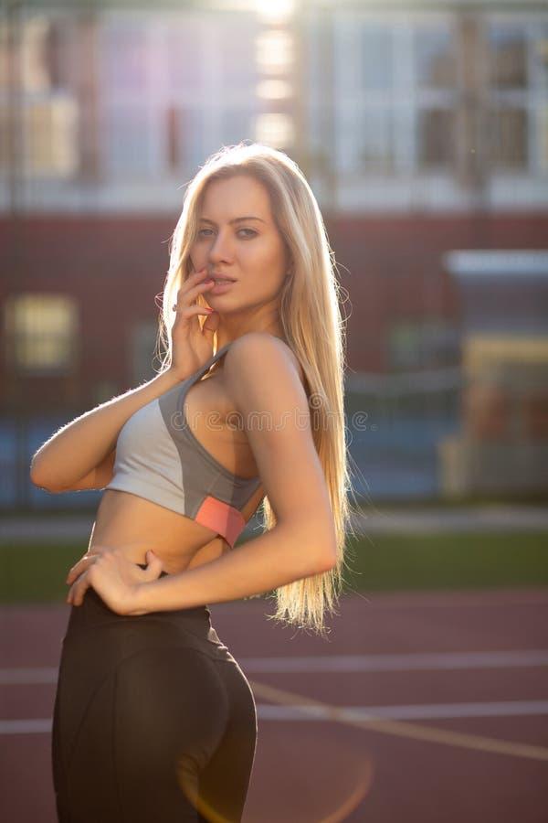 Verleidelijke geschikte vrouw met opgeleid lichaam in sportkleren die stellen royalty-vrije stock afbeeldingen
