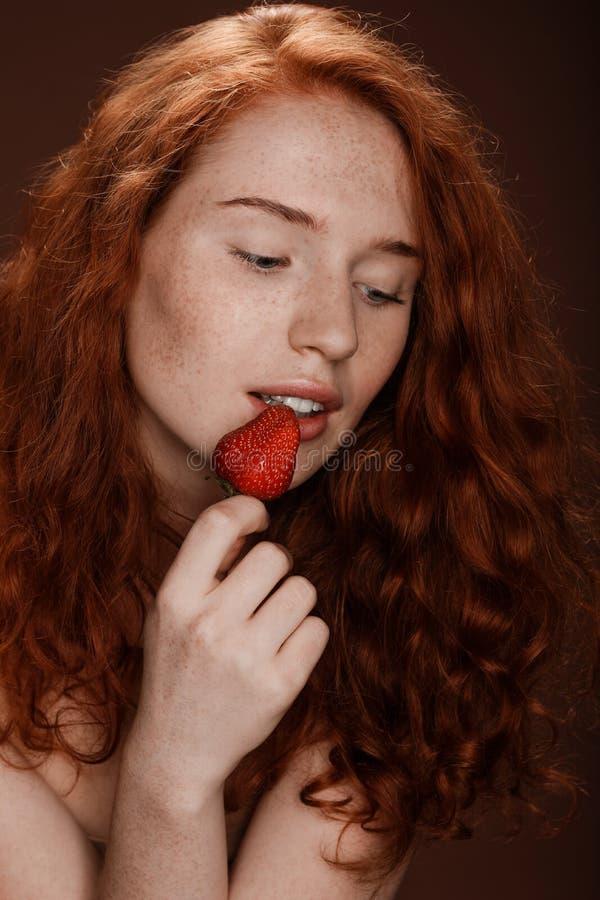 Verleidelijke roodharigevrouw die rode aardbei, op bruin eten royalty-vrije stock fotografie