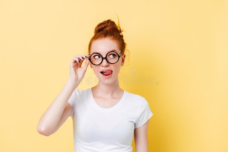 Verleidende gembervrouw die in oogglazen haar lippen likken royalty-vrije stock afbeelding