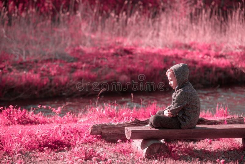 Verletzbarer Junge an der Flussseite lizenzfreie stockbilder