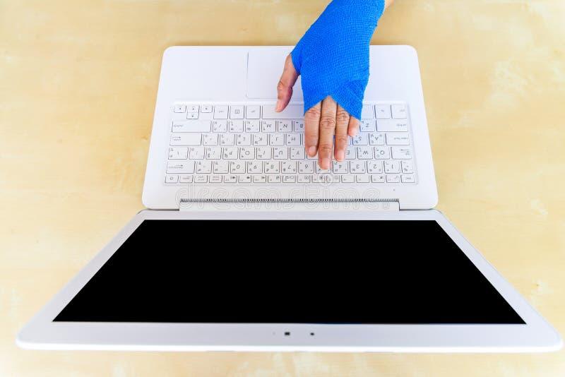 verletzte Frau mit blauer elastischer Binde an Hand, arbeitend an lapt stockbild