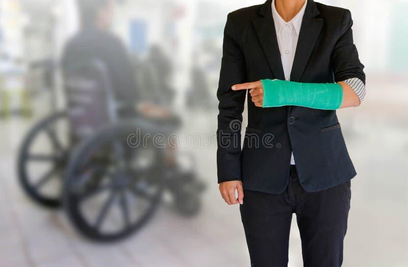Verletzte Geschäftsfrau mit Grün warf an Hand und bewaffnet auf verwischt lizenzfreies stockfoto