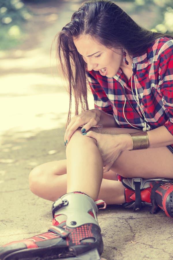 Verletzte junge Frau, die unter den Schmerz sitzen aus den Grund leidet stockbilder