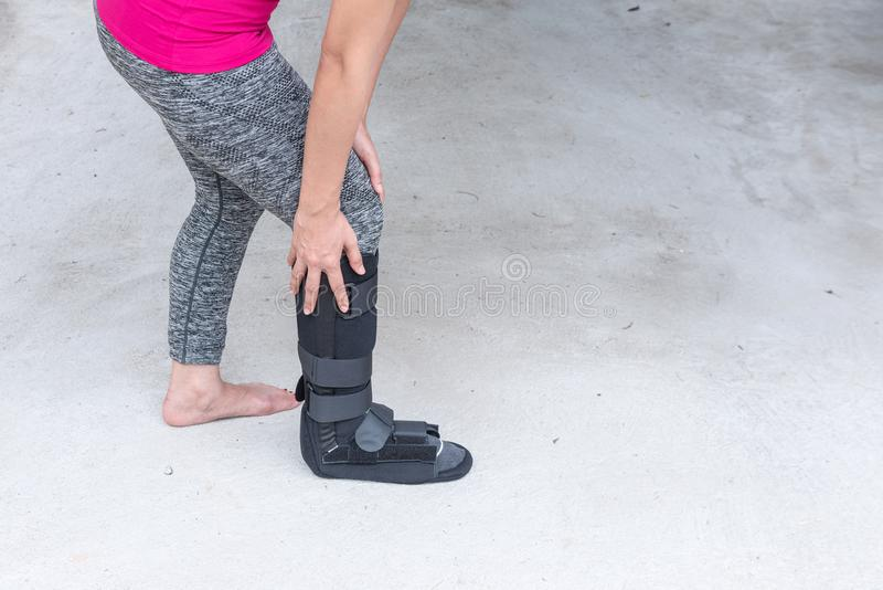verletzte tragende Sportkleidung der Frau mit schwarzer Knöchelklammer auf Bein s stockfoto