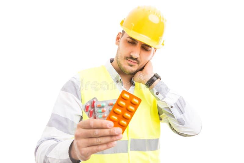 Verletzter Ingenieur oder Erbauer, die Pillenblasen halten lizenzfreie stockfotografie
