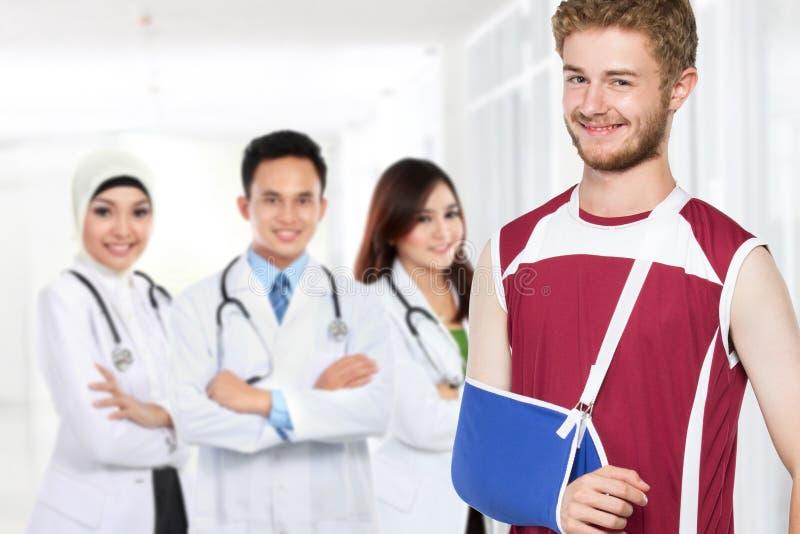 Verletzter Mann mit dem gebrochenen Arm, der vor seinem Doktor steht lizenzfreie stockbilder