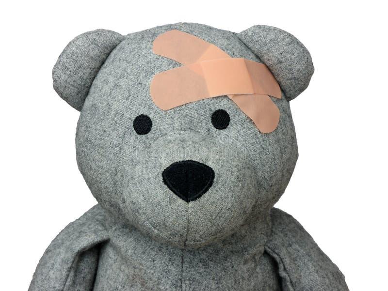 Verletzter Teddy Bear vergipst den lokalisierten Kopf lizenzfreies stockbild