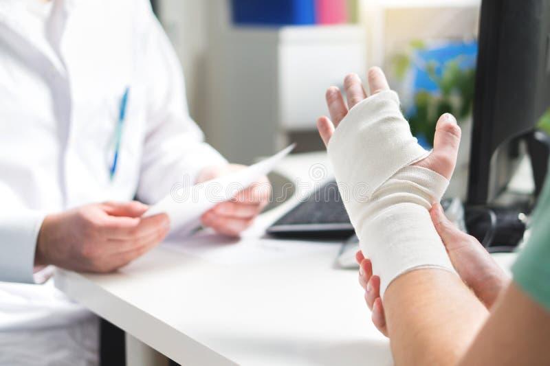Verletztes geduldiges darstellendes Doktor gebrochenes Handgelenk und Arm mit Verband lizenzfreies stockbild