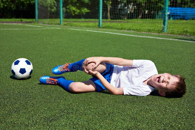 Verletzung des Knies im Jungenfußball stockfotografie