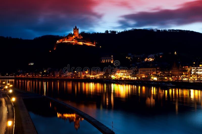 Verlicht stad en kasteel dicht bij rivier royalty-vrije stock foto