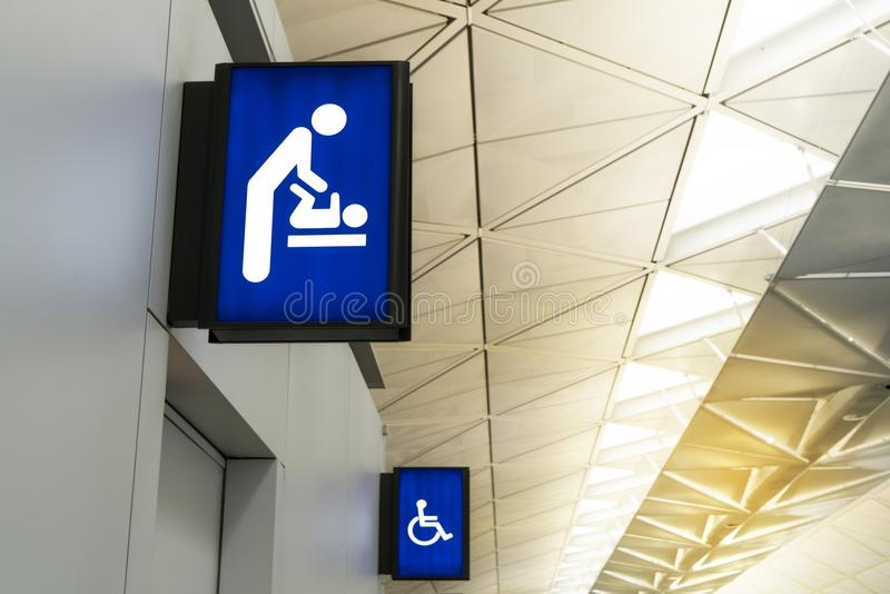 Verlicht uithangbord voor luiervestiaires en gehandicapt toilet in internationale luchthaven met exemplaarruimte voor tekst stock afbeeldingen