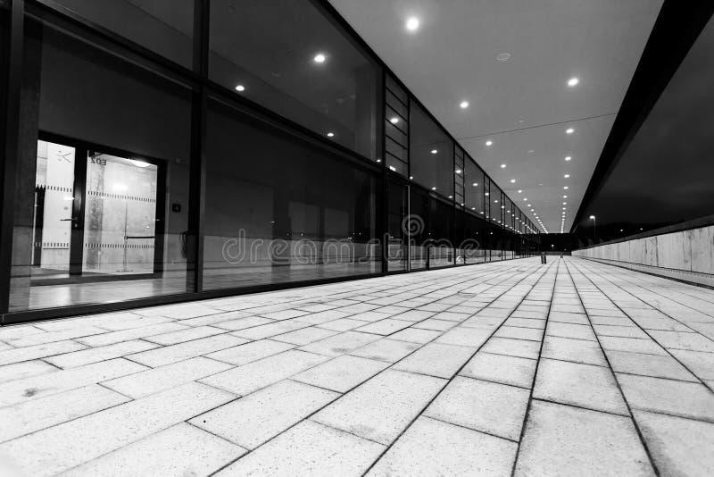 Verlicht voetpassageperspectief langs glas de bouwvoorgevel stock afbeelding