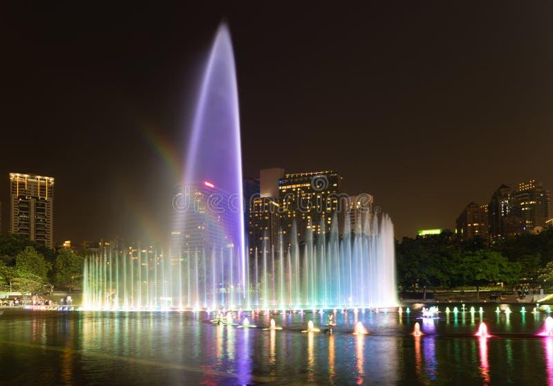 Verlichte fontein bij nacht in moderne stad stock afbeeldingen