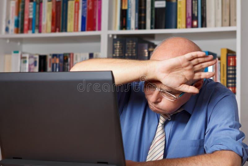 Verlichte oude mens met computer stock foto's