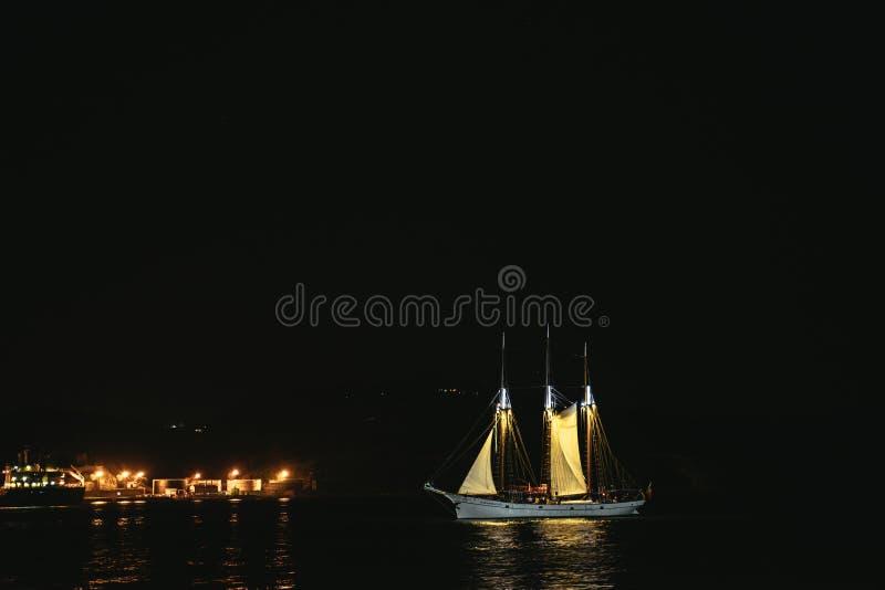 Verlichte zeilboot die haven ingaan bij nacht royalty-vrije stock foto