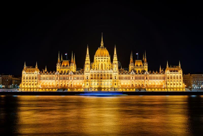 Verlichtend historisch gebouw van het Hongaarse parlement 's nachts op de Donaurivierbedding stock afbeelding