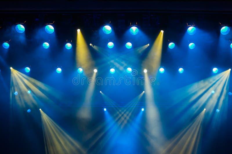 Verlichtingsmateriaal op het stadium van het theater tijdens de prestaties De lichte stralen van de schijnwerper door de rook stock afbeelding
